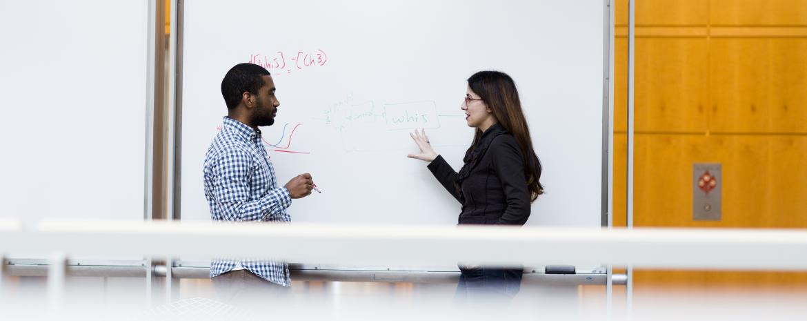 Students talking in front of a whiteboard