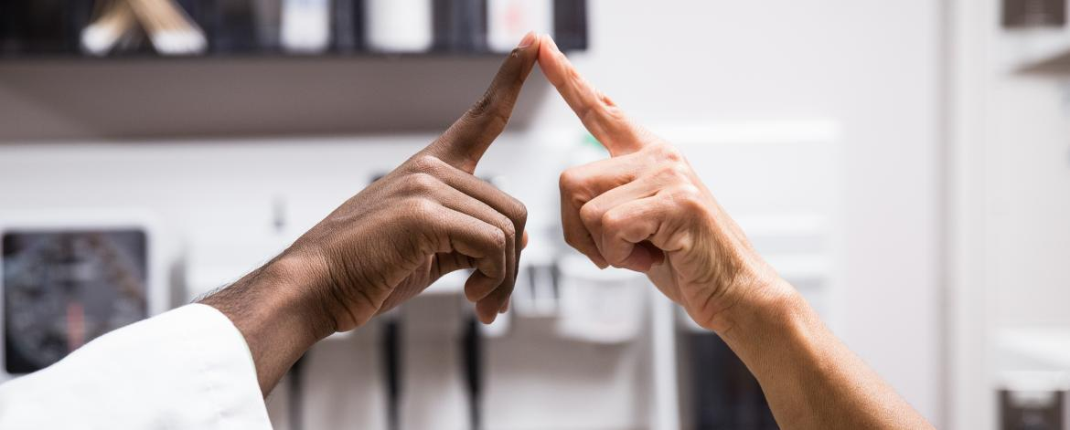 Two people touching the tips of their index fingers together