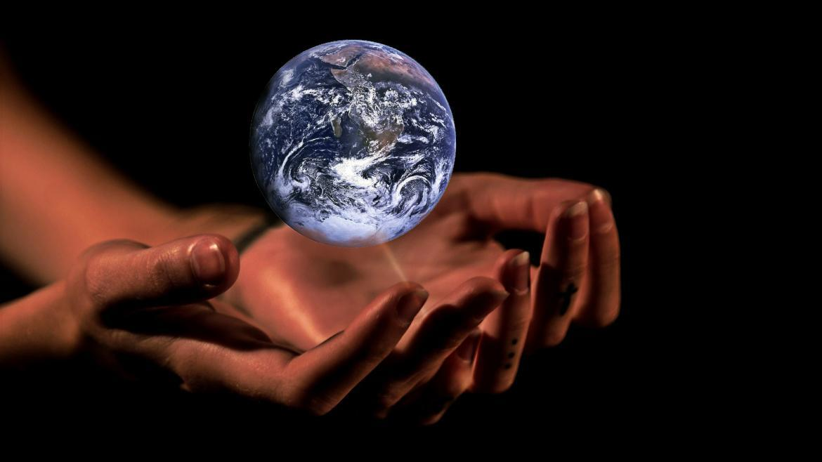 Outstretched hands cradling the planet Earth