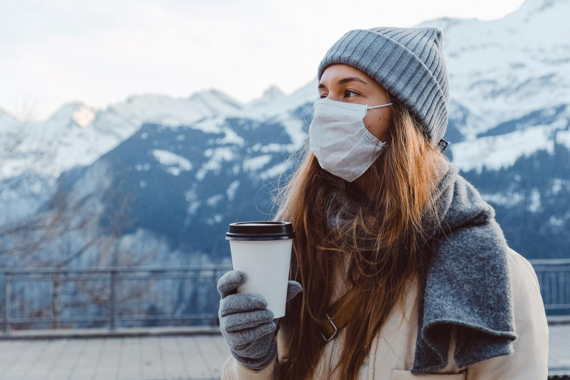Woman standing outside in the cold while wearing a face mask and holding a disposable cup