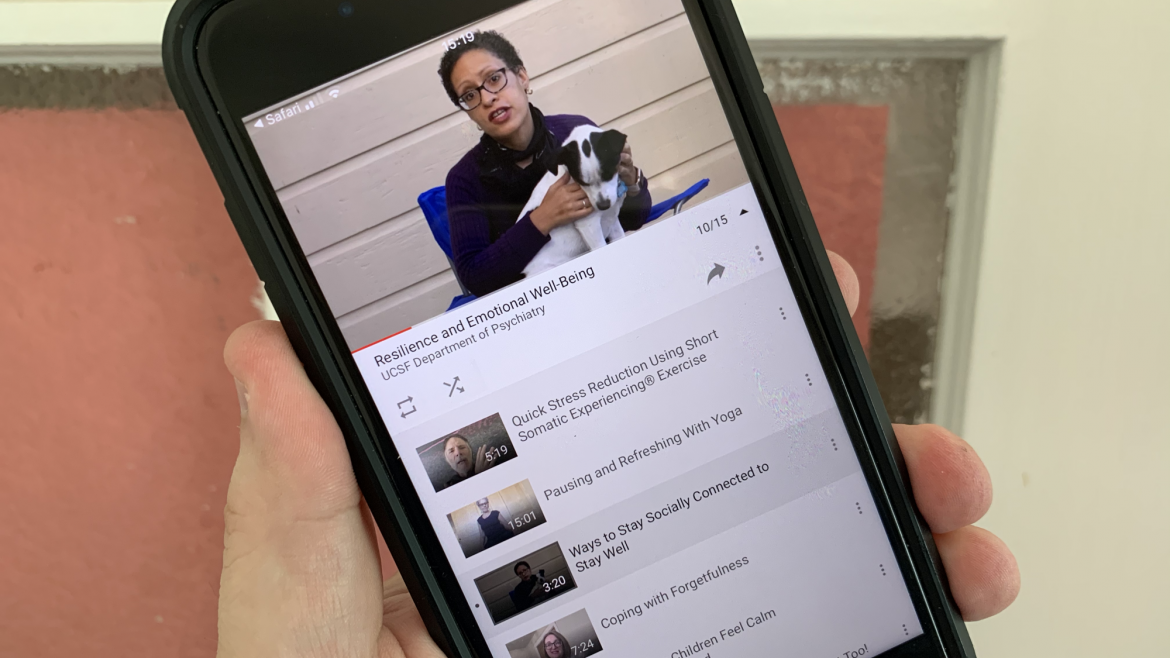 Hand holding an iPhone showing the video series on YouTube