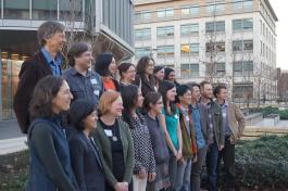 Current and former members of the Doupe Lab stand in front of the Sanders Neurosciences Building on the UCSF Mission Bay campus.