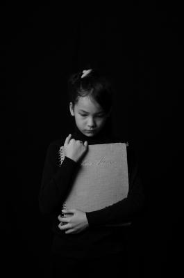 Black and white image of a girl holding a book