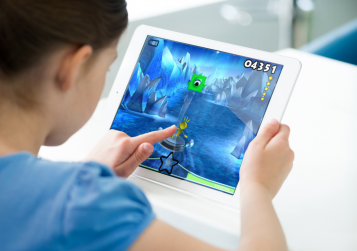 Child playing game on an iPad
