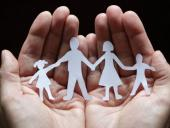 Hands holding a paper cutout family