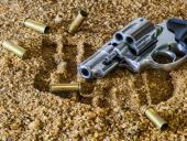 Handgun and empty bullet casings on sand
