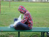 Teen vaping on park bench